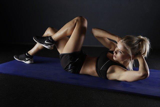 Sportlerin die unsere Buchmuskelübungen zur Stärkung des Sixpacks trainiert