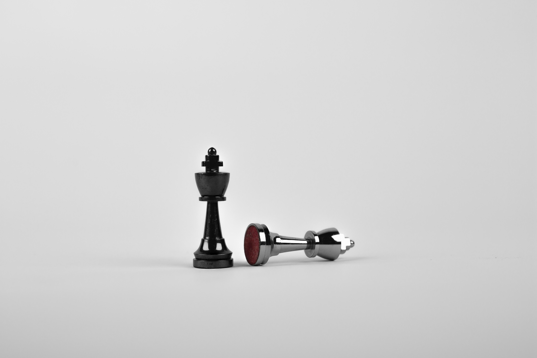 Zwei Schachfiguren und der König stützt die andere Figur