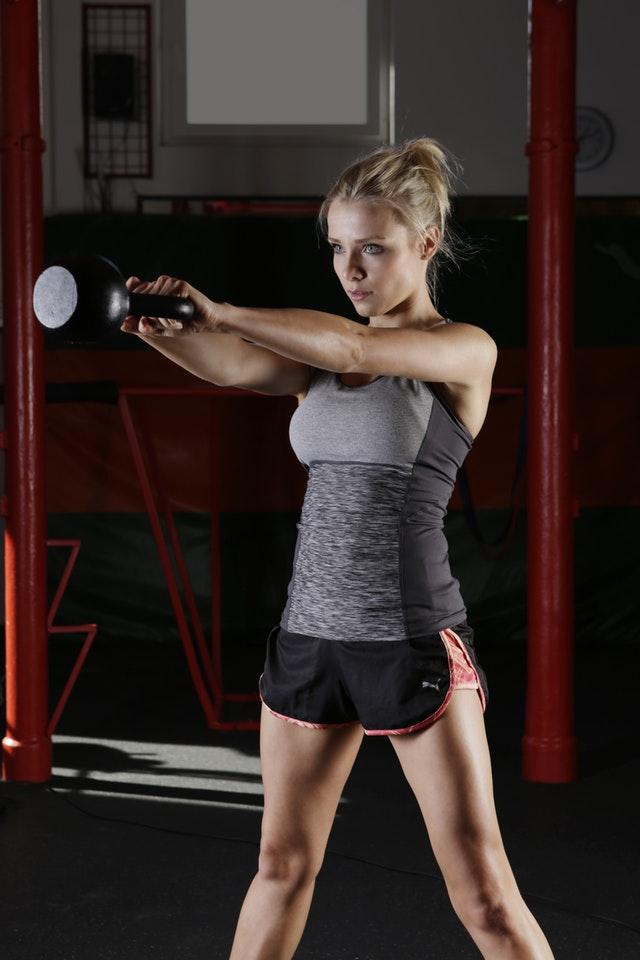 Sportlerin die mit der Rundhantel die Übungen zur Nackenstärkung durchführt
