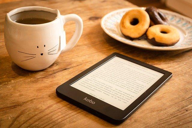 Frühstückstisch mit Kaffee, Donuts und einem Ebook Reader auf dem du dein eigenes lesen kannst