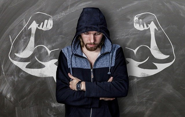 Geknickte Person hinter einer Wand mit gemalten großen Muskelarmen