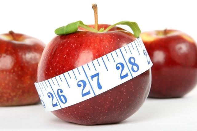 drei rote Äpfel und einer mit einem Maßband auf weißem Hintergrund